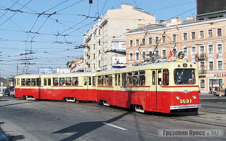 [b]ЛМ-49 (1950 г.) + ЛП-49 (1965 г.).[/b] Трамвайный поезд из вагонов ЛМ-49 и ЛП-49 (ленинградский моторный, ленинградский прицепной образца 1949 года). Они выпускались ленинградским ВАРЗ-1 с 1949 по 1960 и 1968год соответственно. За характерный окрас сиспользованием цвета слоновой кости эти вагоны были прозваны «Слонами». Прицепные вагоны ЛП-49 использовались в поездах с более новыми ЛМ-68 и даже ЛМ-68М – такие составы называли «Динозаврами»